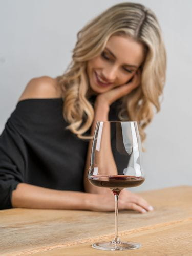 Happy woman sits at a wooden table, a RIEDEL Winewings Cabernet glass filled with red wine standing in front of her.