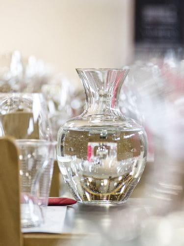 Water filled RIEDEL decanter Apple NY on a set table.