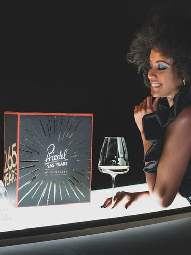 A woman stands at an illuminated bar counter with a white wine filled Winewings Sauvignon Blanc glass and a sales box on it.