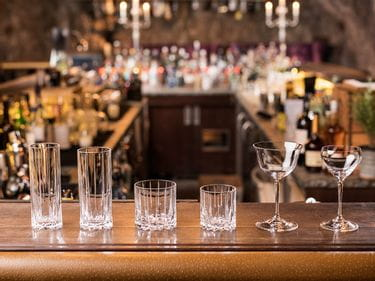 Empty RIEDEL Drink Specific Glassware on a bar counter