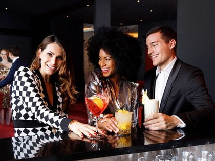 Three people enjoying drinks from RIEDEL cocktail glasses