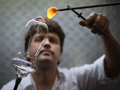 Glassblower at work - creating a hand-made wine glass