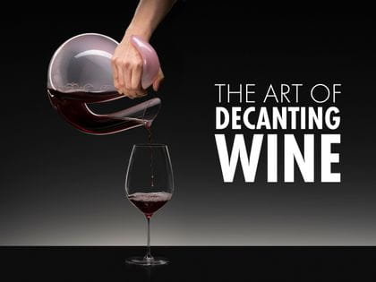 A hand decanting red wine from an Ayam Rosa decanter into a a RIEDEL Performance Cabernet.