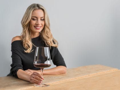 A smiling, blonde woman sits at a wooden table, looking down at a red wine filled RIEDEL Winewings Cabernet Sauvignon glass she holds by the stem.