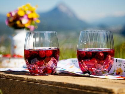 Picknick-scenery on a summer meadow with mountain view. 2 mixed drinks served in Tumbler Collection Optical O Longdrink.