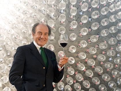 Georg Riedel by a wall of wine glasses