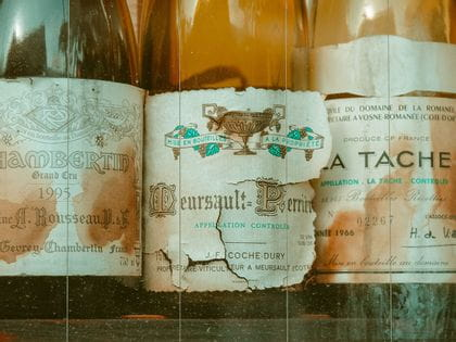 Old wine bottles with peeling stained labels