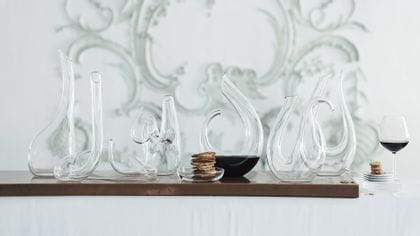 A group of modern RIEDEL decanters on a table