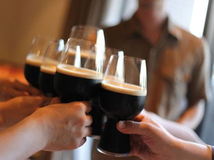 A group raising Craft Beer Stout glasses in cheers