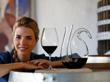 Woman leans on a large wine barrel with a RIEDEL Ouverture Double Magnum and a RIEDEL Ayam decanter both filled with red wine
