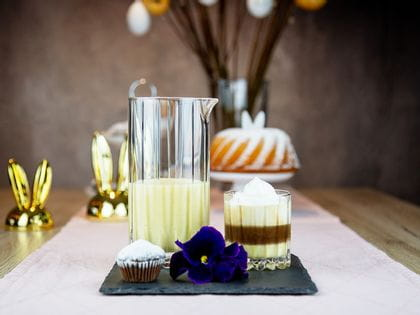 Egg liqueur in a decorative shaker and Neat glass filled with advocaat coffee