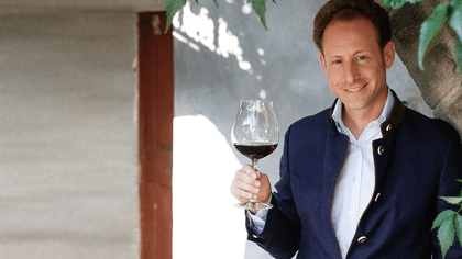 Maximilian J. Riedel leaning on a wall and holding a filled New World Pinot Noir glass.