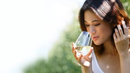 A woman smelling on a Riesling out of a O Wine Tumbler Riesling.