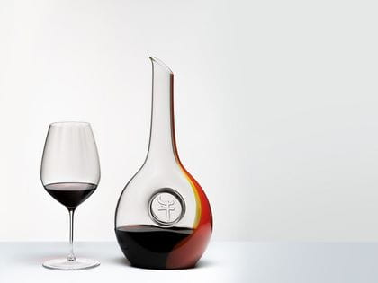 RIEDEL Winewings Cabernet Sauvignon glass and RIEDEL Chinese Zodiac Ox Decanter filled with red wine stand on a light ground