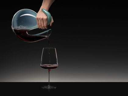 A hand decanting red wine from an Ayam Rosa decanter into a a RIEDEL Winewings Cabernet.