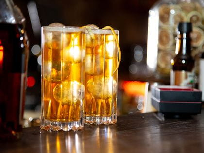 Two filled Drink Specific Glassware Highball tumblers on a bar