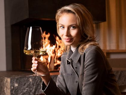 Winewings Riesling glass held by woman in front of fire