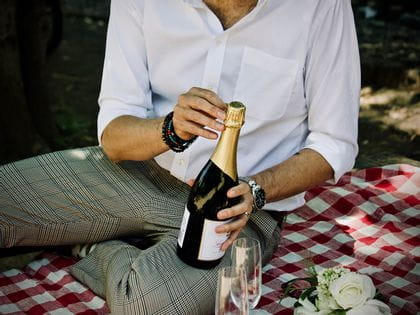 Man opening a bottle of champagne on a picnic rug