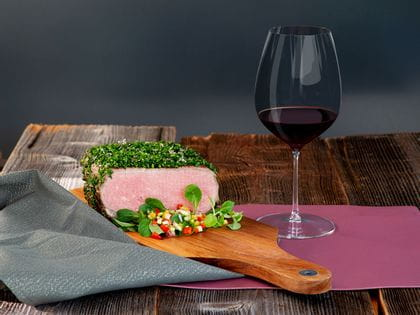 Herb-coated roast beef accompanied by a glass of Cabernet Merlot