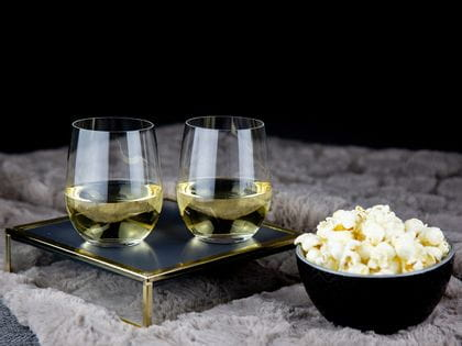 Two white wine filled RIEDEL O Wine Tumbler Viognier/Chardonnay stand on a small tray. Next to the tray a small black bowl with popcorn is placed.