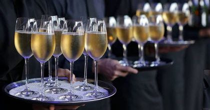 A row of waiters holding trays of full champagne flutes