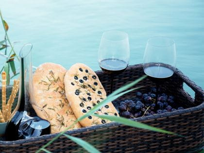 A brown picnic basket filled with 2 glasses of red wine, a decanter, 2 Italian focaccia, grapes and grissini floats on a lake