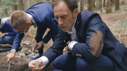 Maximilian Josef Riedel kneels in the forest floor and looks at the historical find.