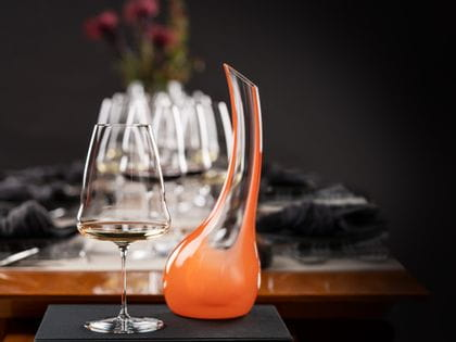 In a room with dark walls, a RIEDEL Winewings Riesling glass filled with white wine and an unfilled Cornetto Confetti Decanter orange stand on a black book placed at the front of a set table.