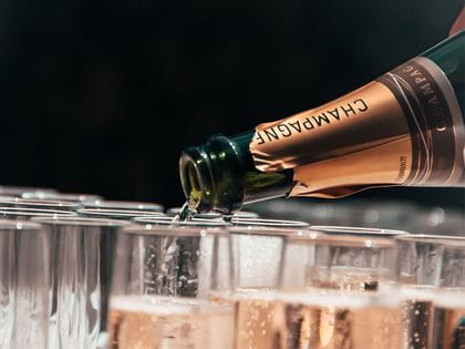 Bottle of pink champagne poured into champagne flutes